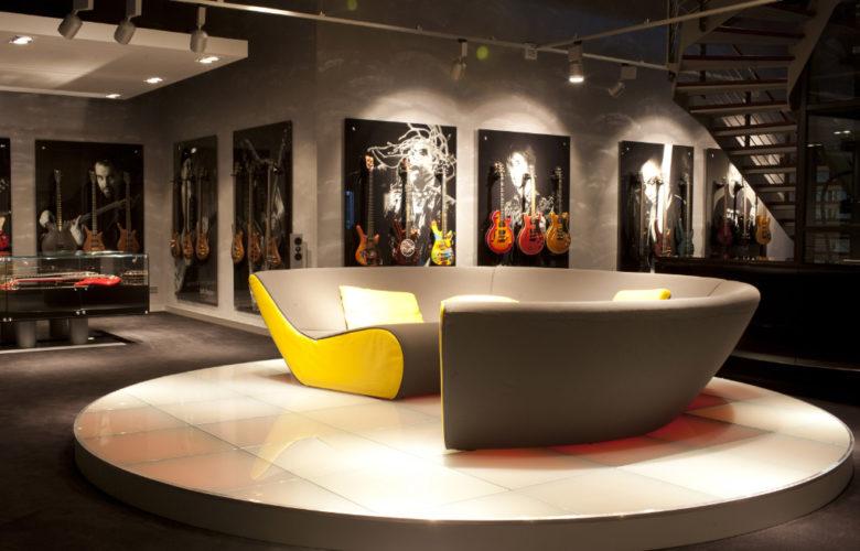 Man sieht ein rundes Sofa auf einem runden Podest. Im Hintergrund E-Gitarren und E-Bässe