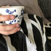 Couch und Hand mit Tasse