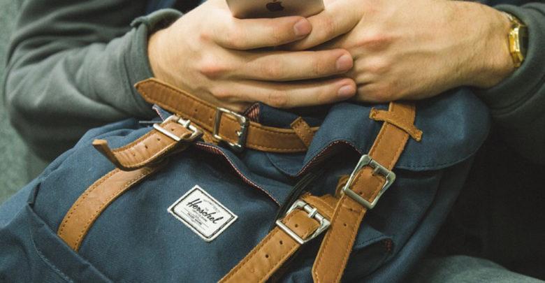 Mann mit Smartphone in der Hand und Rucksack