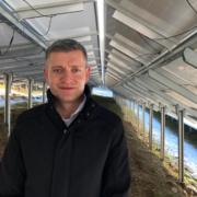 Energiemanager Alexander Wölfel unter der Photovoltaikanlage