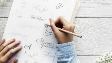 Kalligrafie mit Frauenhand auf weißem Tisch