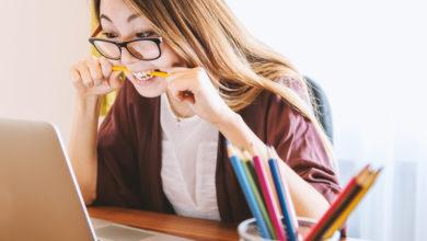 gestresste Studentin vor dem Laptop mit Stift zwischen den Zähnen