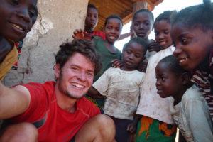 Kinder in Sambia helfen Anselm beim Flicken seines Rads
