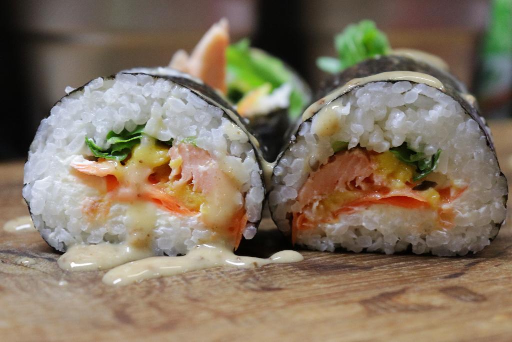 Sushi mit geräuchertem Saibling, Rucola und Karotten, garniert mit einer Sesamcreme. Foto: Sabine Heid
