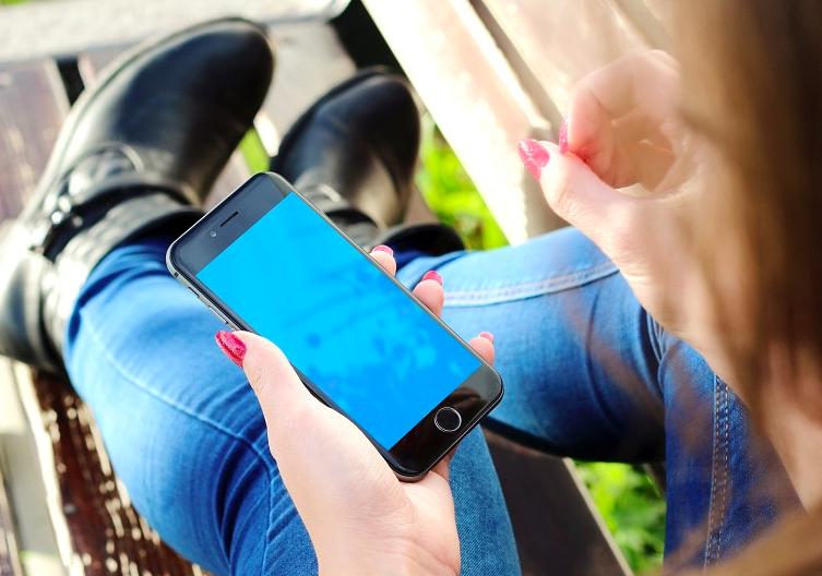 Smartphone in Frauenhand auf Parkbank