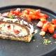Erdbeer-Biskuitrolle mit Pistazien auf einem Teller. Foto: Redaktion