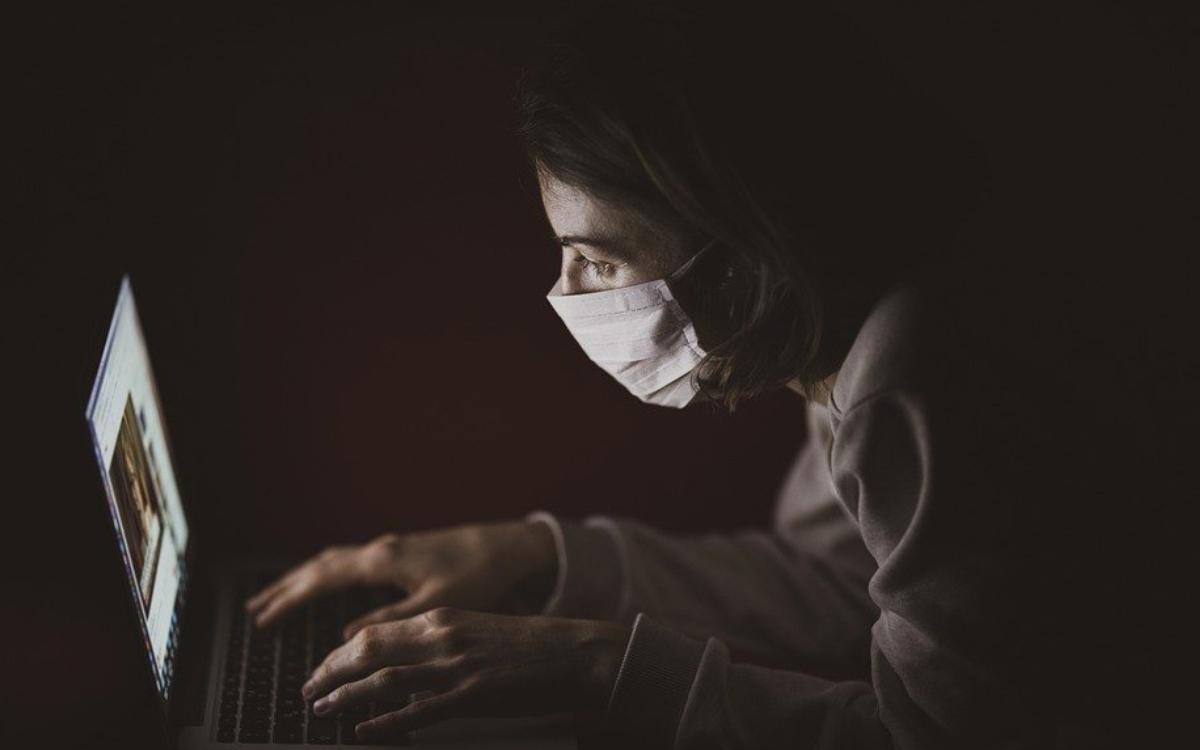 Mit Gesichtsmaske am Laptop in Zeiten von Coronavirus. Symbolbild: Pixabay.