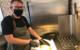 Hannes Frach schneidet im Focacciala sein selbst gebackenes Brot auf. Foto: Christoph Wiedemann
