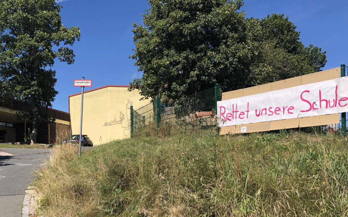 """""""Rettet unsere Schule"""" steht auf einem Transparent vor der Grundschule Schnabelwaid. Eltern, Kinder und Politik kämpfen für den Erhalt der Schule. Foto: Frederik Eichstädt"""