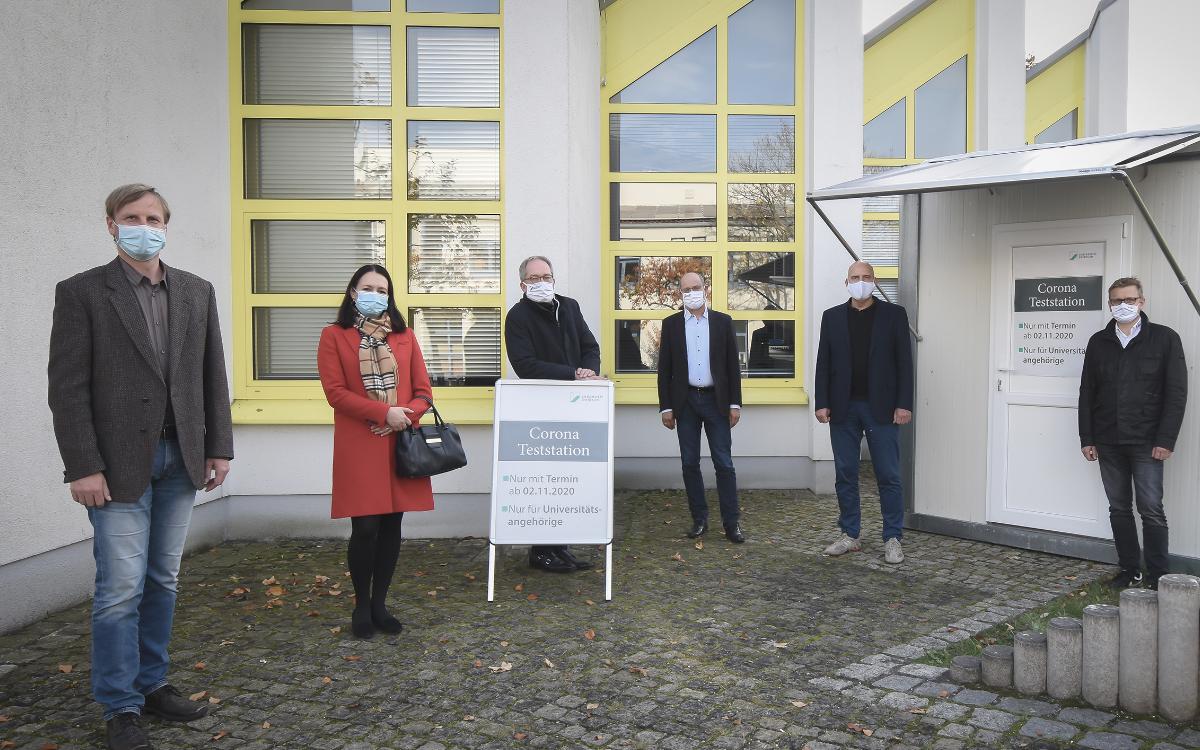 An der Corona-Teststation auf dem Bayreuther Unicampus, v.l.: Dr. Reiner Hofmann (Medizincampus Oberfranken und Universität Bayreuth), Monika Pizon (Ph.D.) vom Labor Dr. Pachmann, Universitätspräsident Prof. Dr. Stefan Leible und Kanzler Dr. Markus Zanner, Prof. Dr. mult. Eckhard Nagel (Institut für Medizinmanagement und Gesundheitswissenschaften) sowie Markus Ruckdeschel (BRK). Dr. Klaus von Stetten vom Bayreuther Gesundheitsamt konnte den Fototermin leider nicht wahrnehmen. Foto: UBT