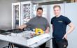 Bernd Zeilmann (im Bild links), Geschäftsführer der Richter R&W Steuerungstechnik GmbH in Ahorntal, und Sebastian Regus, Ausbildungsmeister und Montageleiter, präsentieren Komponenten für den intelligenten Energieknoten (IEK). Für das Baukastensysten stehen verschiedene Module zur Verfügung, unter anderem ein iMSys- und Einspeisemodul (iMSys: intelligentes Messmodul, im Bildvordergrund liegend) und ein Niederspannnungsverteilermodul (im Bildhintergrund stehend). Bild: Anja Grabinger / Fraunhofer IISB