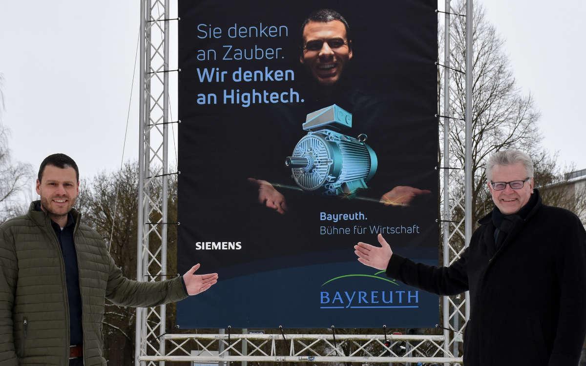 Gemeinsam mit Dominik Herrmann bestaunte Oberbürgermeister Thomas Ebersberger als erster das neue Werbemotiv der Bayreuther Standortkampagne, für das der Technische Projektleiter der Siemens AG Modell stand. Foto: Andreas Türk