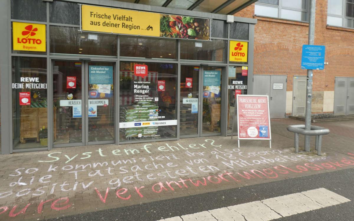 Corona-Ausbruch in einem Rewe in Bayreuth: Kunden haben mit Kreide vor dem Supermarkt eine Botschaft geschrieben. Foto: privat