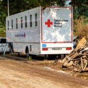 Einsatz des DRK bei der Hochwasserkatastrophe in Rheinland-Pfalz: mobile Krankenstation zur medizinischen Versorgung (MMVE) an einer Strasse neben Schuttbergen. Bild: Philipp Köhler/DRK