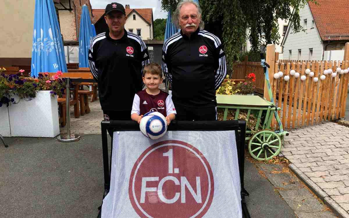 Der 1. FC Nürnberg hat dem kleinen Ryan Hacker aus Bayreuth ein Geschenk überreicht. V.l.n.r.: Bernd Reindl, Camp-Leiter 1. FCN, Ryan Hacker und Klaus